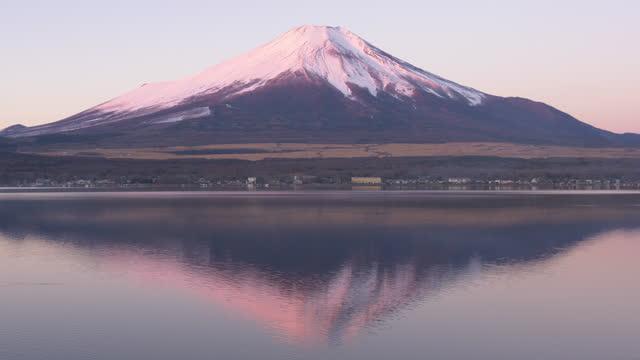 red mt. fuji reflected in lake yamanaka in the winter morning - 山梨県点の映像素材/bロール