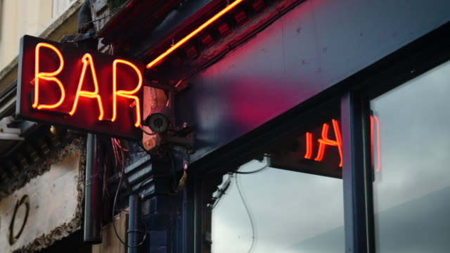 vidéos et rushes de a red neon bar sign is reflected in the window - vie sociale