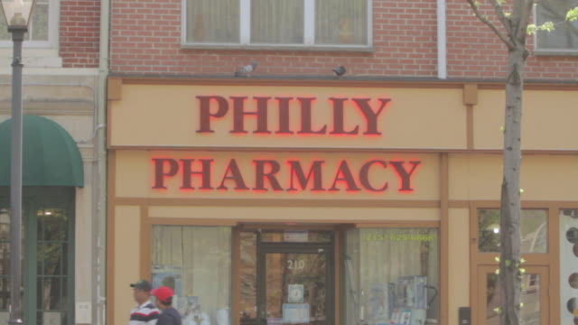 la red neon sign for philly pharmacy, with pedestrians and traffic going by / philadelphia, pennsylvania, united states - front view stock videos & royalty-free footage