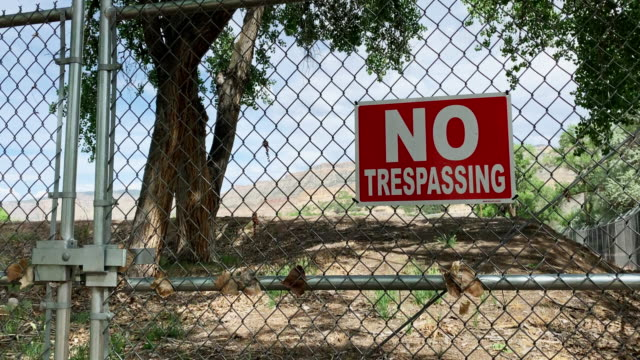 "a red ""no trespassing"" sign hanging on a locked chainlink gate guarding property on a sunny day - no trespassing stock videos & royalty-free footage"