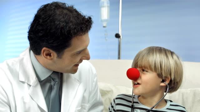 vídeos de stock, filmes e b-roll de hd: red nose médicos entretenimento para crianças - enfermeira pediátrica