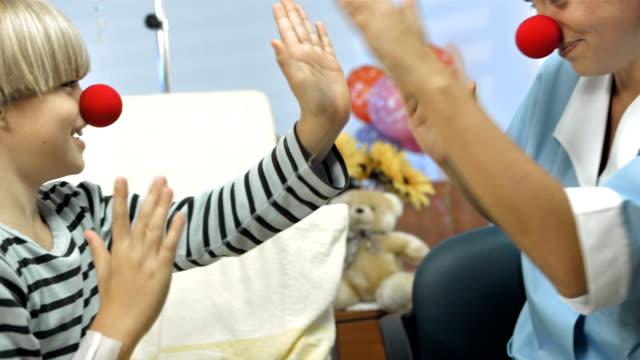 vídeos de stock, filmes e b-roll de hd: red nose enfermeira entretenimento para crianças - enfermeira pediátrica