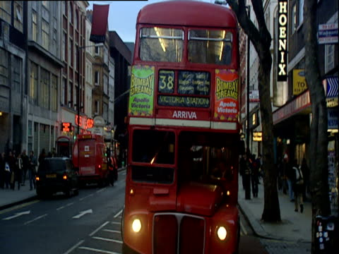 red number 38 bus travels towards camera along charing cross road destination victoria station - charing cross stock videos and b-roll footage