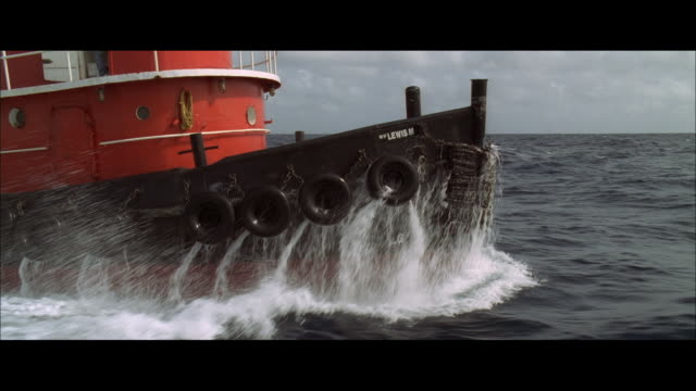 vidéos et rushes de ws a red oceangoing tugboat rolling in choppy water and turning away - remorqueur