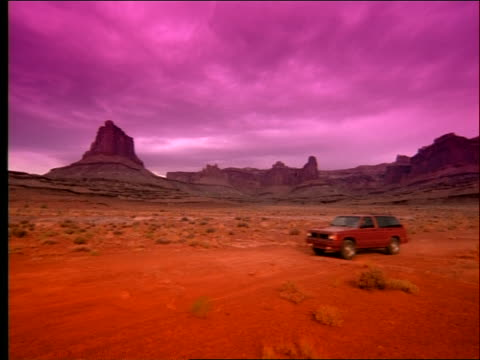red off-road vehicle driving in desert with buttes in background / filter - southwest usa stock videos and b-roll footage