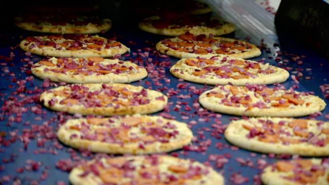 vídeos de stock e filmes b-roll de red onion and pepperoni toppings added to pizza - indústria de comidas e bebidas