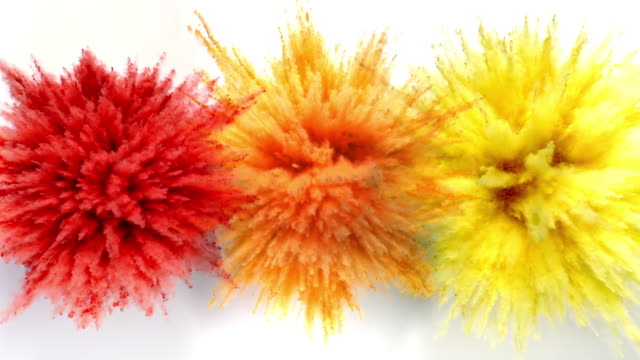 vídeos de stock e filmes b-roll de red, orange and yellow colored powder exploding towards camera at the same time in close up and super slow-motion, white background - três objetos