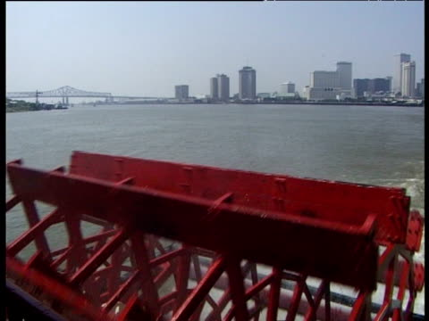 Red paddle turns on steamboat splashing water with skyline of New Orleans in background on Mississippi river
