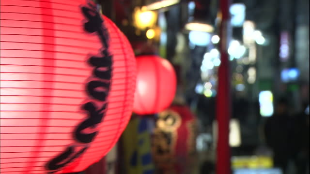 red paper lanterns sway on a busy tokyo street. - catering building stock videos & royalty-free footage