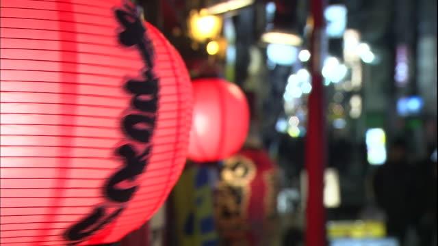 vídeos de stock e filmes b-roll de red paper lanterns sway on a busy tokyo street. - edifício de restauração