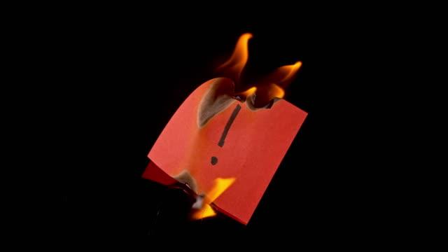 vídeos de stock e filmes b-roll de slo mo ld red paper with exclamation mark on it burning in fire - ponto de exclamação