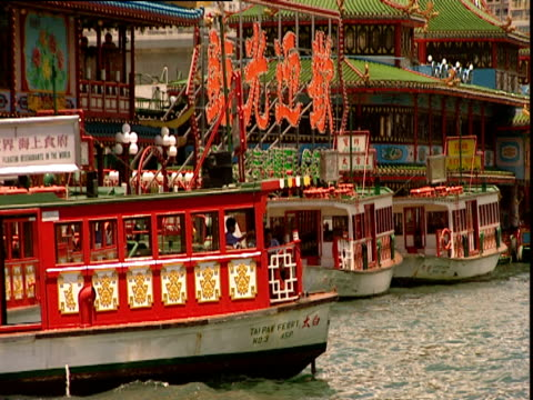 red passenger ferry passes in front of colourful harbour buildings and chinese script signs hong kong - non western script stock videos & royalty-free footage