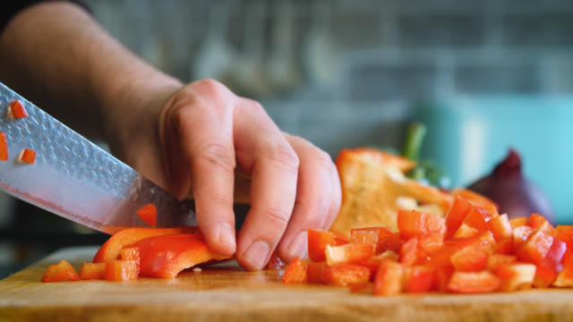 a red pepper is sliced and diced with a knife - bell pepper stock videos & royalty-free footage