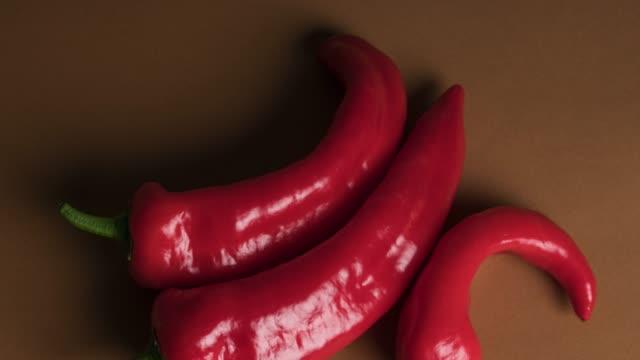 red pepper over brown background - sfondo marrone video stock e b–roll