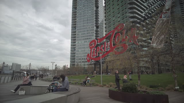 red pepsi cola sign in long island city's gantry plaza state park during the coronavirus pandemic with people wearing face masks in new york city,... - office block exterior stock videos & royalty-free footage