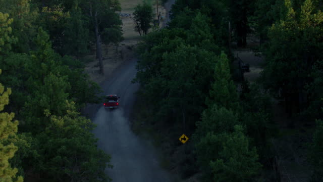 vidéos et rushes de red pickup truck driving a gravel road through trees - pick up