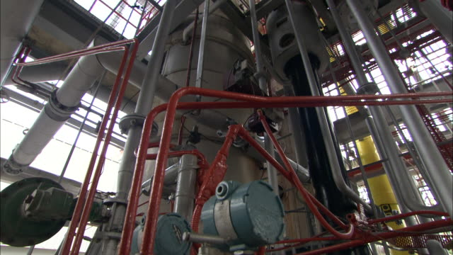 red pipes crisscross over machinery in a bottling plant. - crisscross stock videos & royalty-free footage