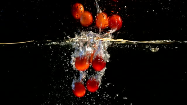 red plum. fruits falling into water against. black background.slow motion - plum stock videos & royalty-free footage