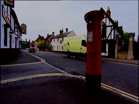 red post box traffic passes behind - mailbox stock videos and b-roll footage