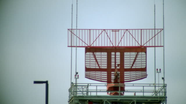 red radar antenna spinning on top of control tower at airport / airliner taking off in background - 1998 stock videos and b-roll footage