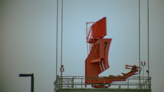 Red radar antenna spinning on top of control tower at airport / airliner taking off in background