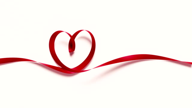 red ribbon forming a heart shape on white background 4k resolution - christmas gift stock videos & royalty-free footage