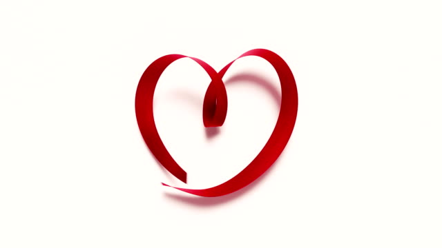 red ribbon forming a heart shape on white background 4k resolution - tied bow stock videos & royalty-free footage