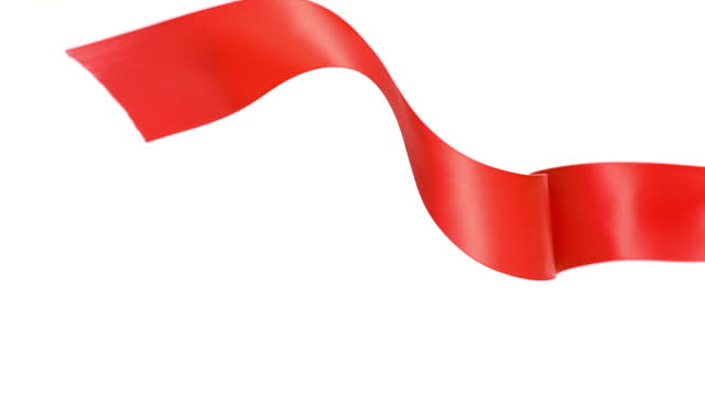a red ribbon on white background, for celebration events and party for new year, birthday party, christmas or any holidays, waiving and curling in super slow motion and close up - banner sign stock videos & royalty-free footage