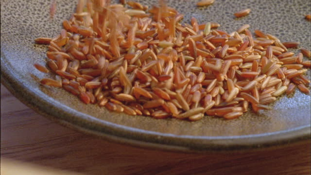 cu, red  rice falling on plate - overflowing stock videos & royalty-free footage