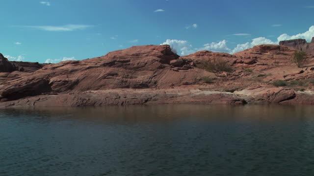 vídeos de stock e filmes b-roll de red rock formations surrounding lake powell - arenito