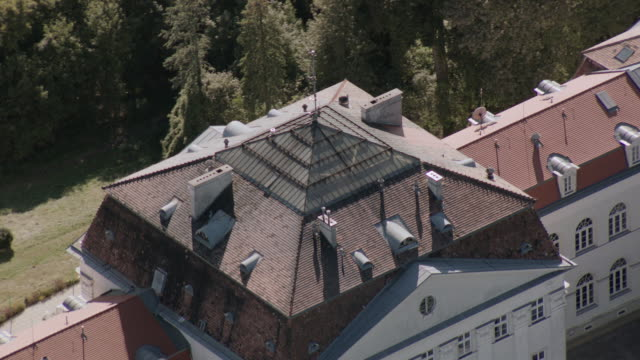aerial red roof on grand, multi-story, white estate atop wooded, green hill - stockwerk stock-videos und b-roll-filmmaterial