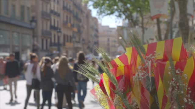 red roses on sant jordi catalan celebration in barcelona. people walking defocus on background. - スペイン国旗点の映像素材/bロール