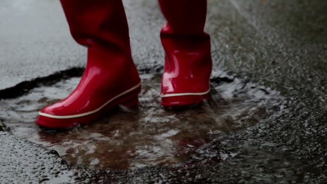 CU TD Red rubber boots dancing in puddle on roadside / Copenhagen, Sjaelland, Denmark