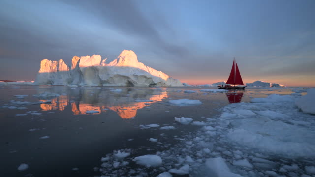 red sailboat cruising among floating icebergs in disko bay - greenland stock videos & royalty-free footage