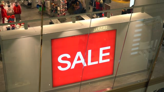 Red Sale Sign in Crowded Shopping Mall