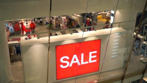 vídeos y material grabado en eventos de stock de cartel de venta roja en el centro comercial abarrotado - rebajas