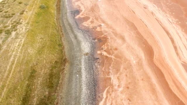 aerial: red salt lake surface with therapeutic mud along shores - backwater stock videos & royalty-free footage