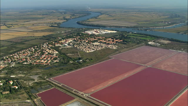 aerial, red salt pans and river rhone in background, provence, france - rhone river stock videos & royalty-free footage