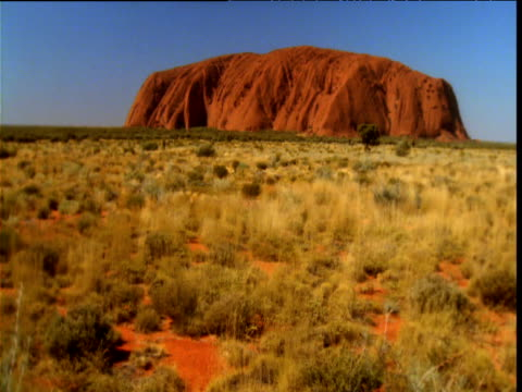 red sandstone of uluru stands over outback, northern territory, australia - エアーズロック点の映像素材/bロール