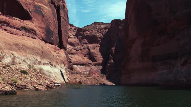 red sandstone rock formations tower over a still river. - sandstone stock videos & royalty-free footage
