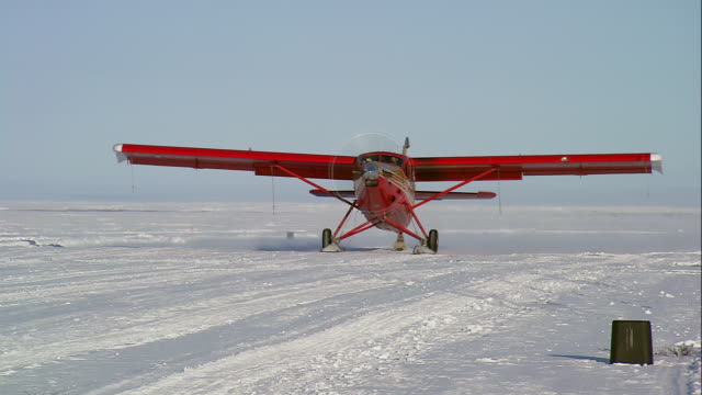 ts red single-engine light plane on skis taking off on layered packed and soft snow / alaska, united states - arctic national wildlife refuge stock videos & royalty-free footage