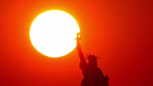A red sky and blazing sun glow behind the Statue of Liberty.