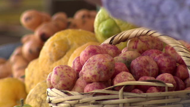 stockvideo's en b-roll-footage met red speckled potatoes in basket with lemons and carrots in b/g, la cancha market, cochabamba, bolivia - bolivia