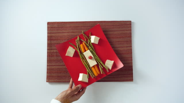 ms ha red square plate with vegetables and tofu artfully arranged being served onto mat - 一人前の量点の映像素材/bロール