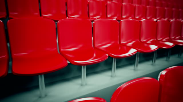 red stadium seats in a row. loopable. - chair stock videos & royalty-free footage