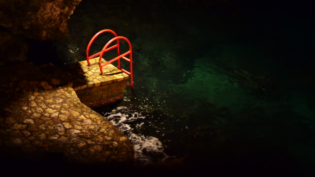 Red stepladder leads to ocean
