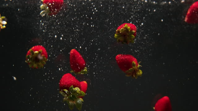 red strawberry fruit in water splash - five objects stock videos & royalty-free footage