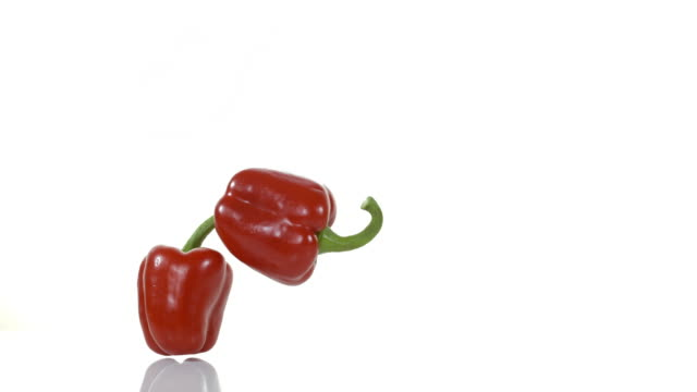 red Sweet Pepper, capsicum annuum, Vegetable falling and Breaking against White Background, Slow motion 4K