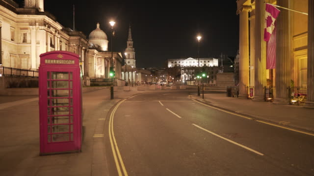 a red telephone box and the eerie quiet atmosphere in central london uk, devoid of people at dusk at trafalgar square - central london video stock e b–roll