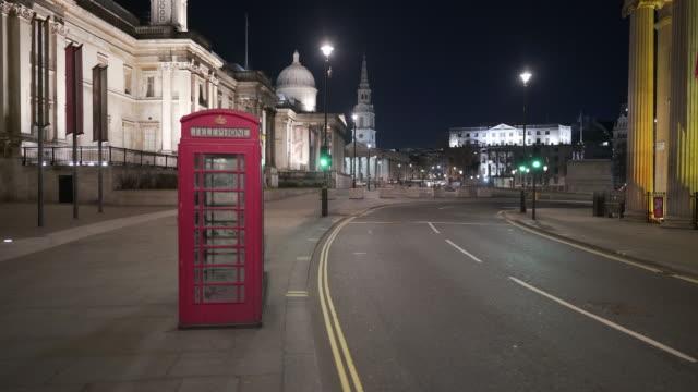 トラファルガー広場の夕暮れ時の人々を欠いた、セントラルロンドン英国の赤い電話ボックスと不気味な静かな雰囲気 - トラファルガー広場点の映像素材/bロール